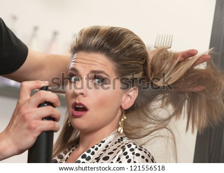Pretty woman is startled by stylist using hair spray