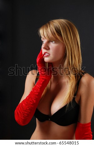 Pretty woman is thinking and looking sideways. She is wearing black lingerie. She is gently touching her face with right hand in red long gloves.