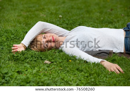 Pretty woman laying on the grass with hands behind head
