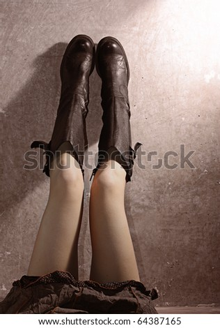 Pretty woman legs in black leather boots.
