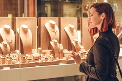Pretty woman looking at jewelry in store window. Customer near jewellery. Dreamy red hair girl chooses silver, gold, diamonds, precious stones. Purchaser