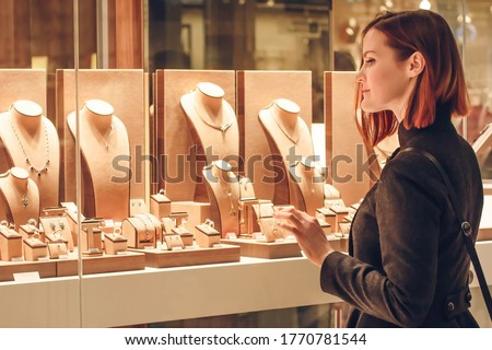 Pretty woman looking at jewelry in store window. Customer near jewellery. Dreamy red hair girl chooses silver, gold, diamonds, precious stones. Purchaser Photo stock ©