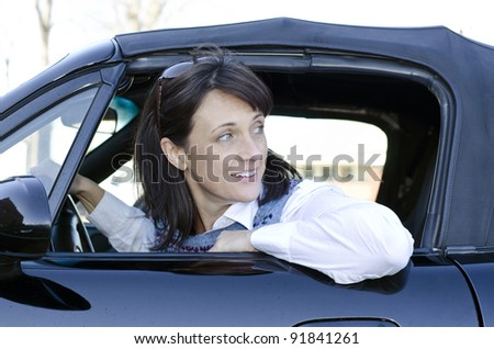 Pretty woman looking behind her as she backs up her car