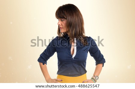 Pretty woman looking lateral over ocher background