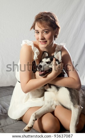 Pretty woman loving her pet husky dog
