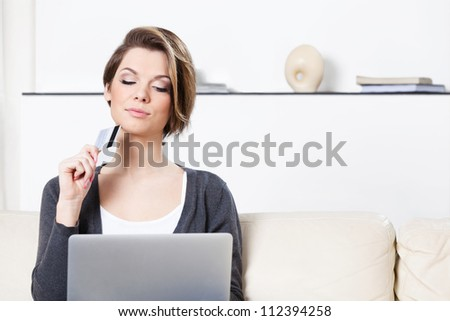 Pretty woman makes purchases through the internet holding credit card - stock photo