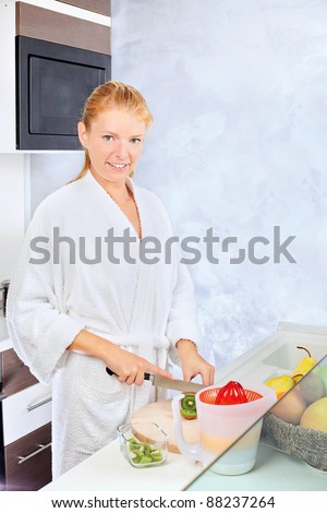 pretty woman making fruit salad in kitchen