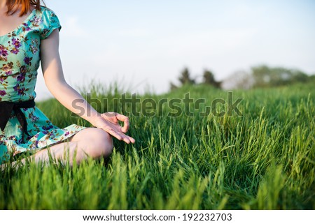 Pretty woman meditate sitting on the grass