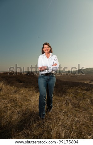 Pretty woman middle aged enjoying outdoors. Standing in grassy dune landscape. Clear sunny spring day with blue sky.