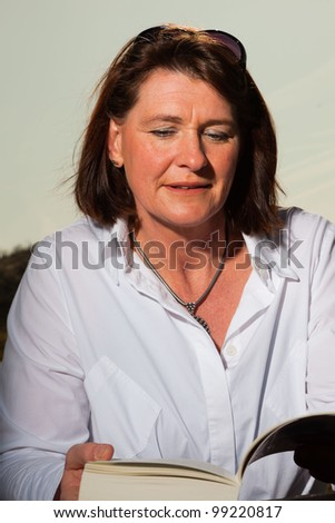 Pretty woman middle aged reading a book and enjoying outdoors. Clear sunny spring day with blue sky.