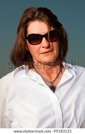 Pretty woman middle aged with sunglasses enjoying outdoors. Clear sunny spring day with blue sky.