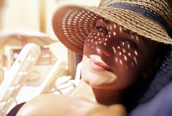 Pretty woman on the beach, closeup portrait of a nice female hides her face from the sun under a straw hat, skin protection, happy healthy summer vacation