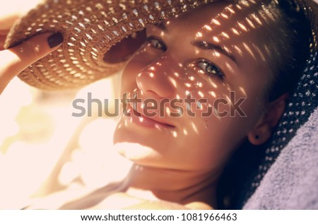 Pretty woman on the beach, closeup portrait of a nice female hides her face from the sun under a straw hat, skin protection, happy healthy summer vacation                                - Shutterstock ID 1081966463
