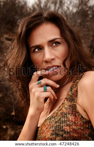 Pretty woman outdoors with her hand to her mouth