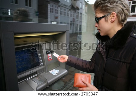 pretty woman outdoortaking cash from an atm machime