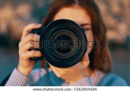 Pretty woman photographer in nature takes a picture