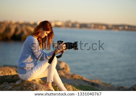 Pretty woman photographer with a camera in her hand takes pictures of nature