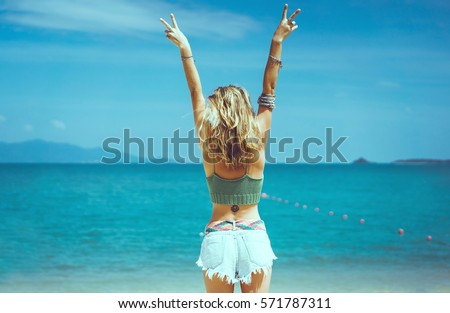 pretty woman posing in the sea, blue sky, hair wild, victory hand up!, outdoor portrait hipster, fashion model, pretty female, denim shorts, hippie, tattoo, hipster girl, Amsterdam, denim shorts,cute