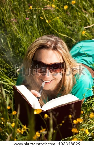 pretty woman reading , and evaporated to an electric cigarette - stock photo