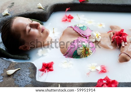 pretty woman relaxing in milk bath with flowers
