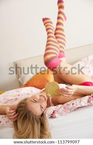 Pretty Woman Relaxing On Bed Eating Breakfast