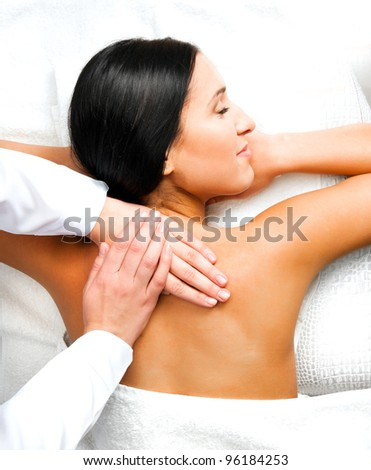 Pretty woman relaxing while getting a back massage at the spa