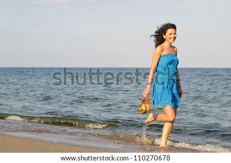 Pretty woman running along the edge of the surf on a sandy beach with her shoes in her hand