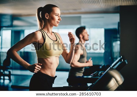 Pretty woman running on treadmill with fit young man on background