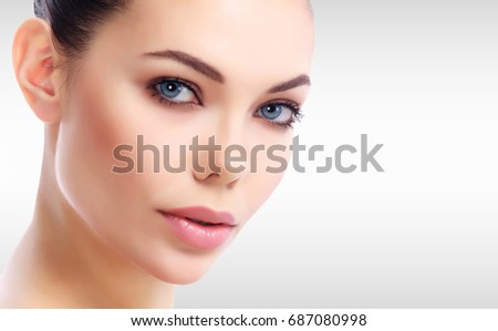 Stock Photo Pretty woman's face against a grey background with copyspace