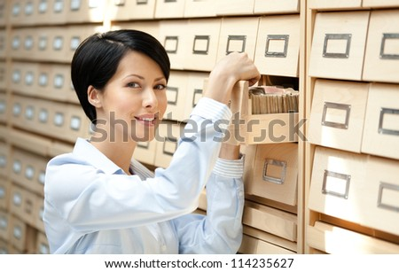 Pretty woman searches something in card catalog composed of set of wood boxes at the library. Education and research