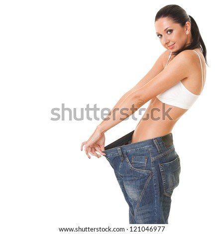 Pretty woman shows her weight loss by wearing an old jeans, isolated on white background