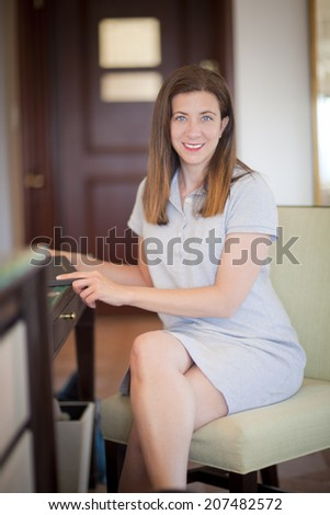 Pretty woman sitting down in hotel room with room service menu