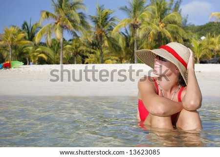Pretty woman sitting in shallow water by a tropical beach