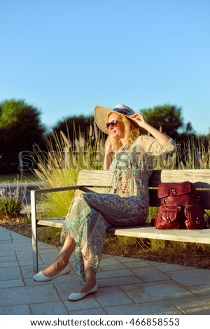 Pretty woman sitting on a park bench at sunset, sunny blue sky outdoors background