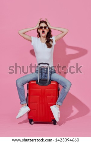 Pretty woman sitting on a red suitcase pink background lifestyle leisure travel destination destination
