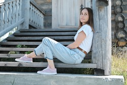 pretty woman sitting on a stairs of old abandoned wooden house. country travelling. woman wearing casual outfit looking asise and smiling. quiet and tranquil place to stay mindful and peaceful.