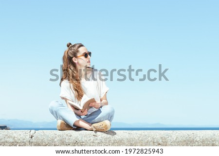 Pretty woman sitting on a stone bench with a book. Studying in a summer sunny day. Stockfoto ©