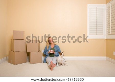 Pretty Woman Sitting on Floor with Cup Next to Moving Boxes and Dog in Empty Room.