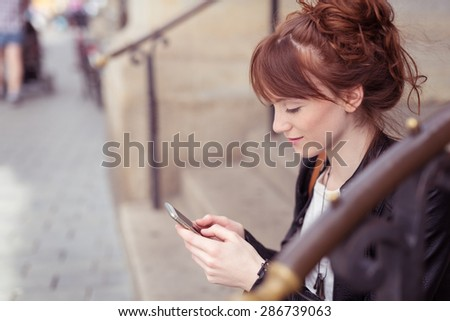 Pretty woman sitting on steps in an urban street to read an sms on her mobile phone, profile view