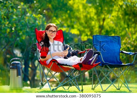 Pretty woman spending time outdoors, sitting in armchair with phone in hands, enjoying vacation in the camping, relaxation in countryside