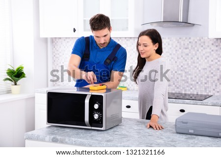 Pretty Woman Standing Near Repairman Repairing Oven Using Digital Multimeter In Kitchen #1321321166