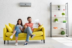 pretty woman using digital table and handsome man reading newspaper while sitting on yellow sofa under air conditioner at home