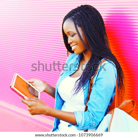 Pretty woman using tablet pc in the city over colorful pink background