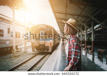 Pretty woman waiting the train at train station for travel in summer. Travel concept.