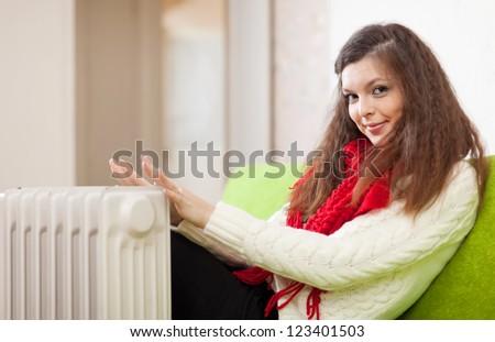 Pretty woman warms hands near calorifer at home