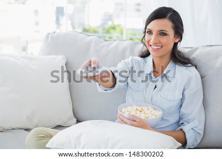 Pretty woman watching tv eating popcorn in her living room