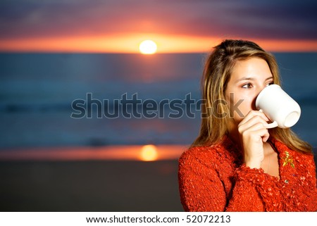 Pretty woman wearing a red wool top drinking a cup of coffee on the beach at sunrise.