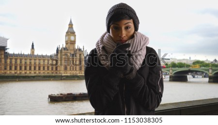 Pretty woman wearing cozy hat and scarf on overcast day in London England