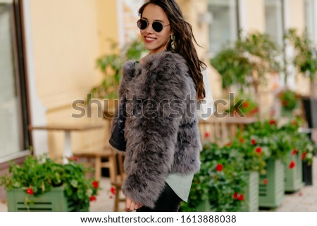 Pretty woman wearing glasses and fur coat walking on the street and smiling on good day. Pretty young lady posing on bright street, waiting friend on avenue.