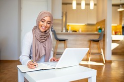 Pretty woman wearing hijab in front of laptop search and doing office work with different face expression isolated in home background - office, business, finance and work station concept